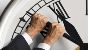 hands stopping large clock